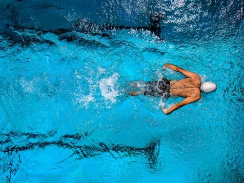 Homme qui nage dans une piscine