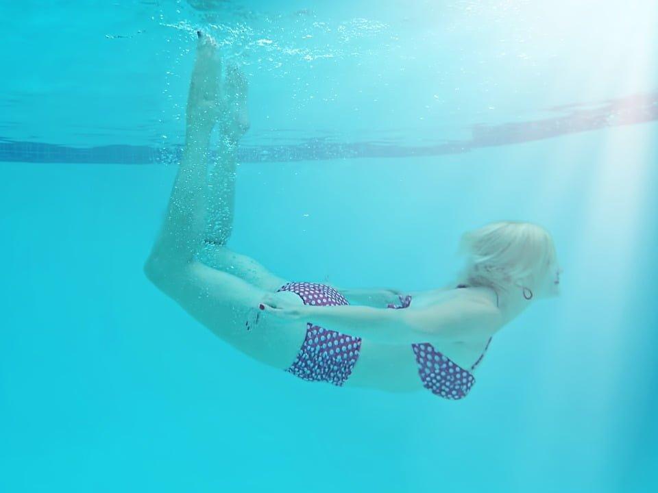 Femme qui nage sous l'eau dans une piscine